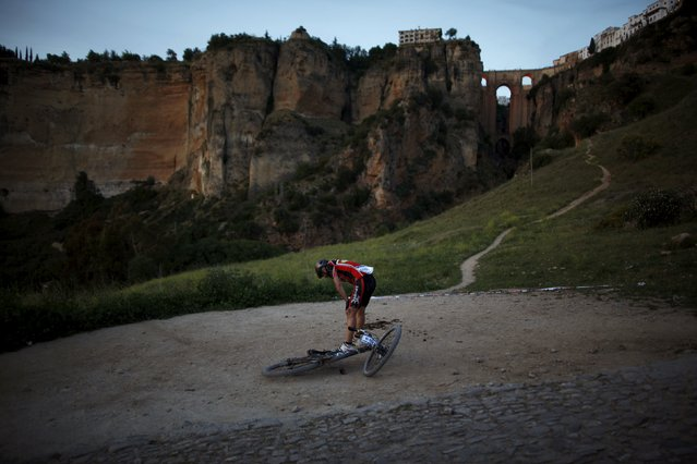 "Spanish mountain biker Alejandro Ortega takes a deep breath as he makes his way to the finish line, in front of ""Puente Nuevo"" (New Bridge), as he participates in the XVIII 101km international competition in Ronda, southern Spain, May 9, 2015. (Photo by Jon Nazca/Reuters)"