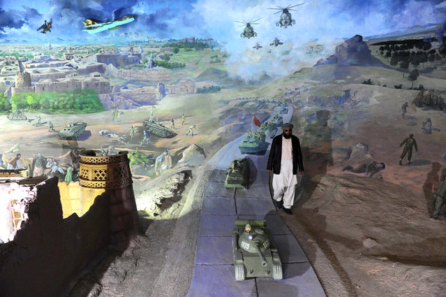 Sheikh Abdullah walks among a display in the Jihad Museum, on February 15, 2014. (Photo by Aref Karimi/AFP Photo via The Atlantic)
