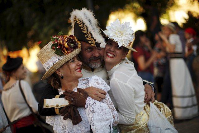 "A man (C) dressed in early nineteenth century French army uniform and women dressed as bourgeoises pose for a friend as they participate in the third edition of ""Ronda Romantica"" (Romantic Ronda) in Ronda, southern Spain, May 16, 2015. (Photo by Jon Nazca/Reuters)"