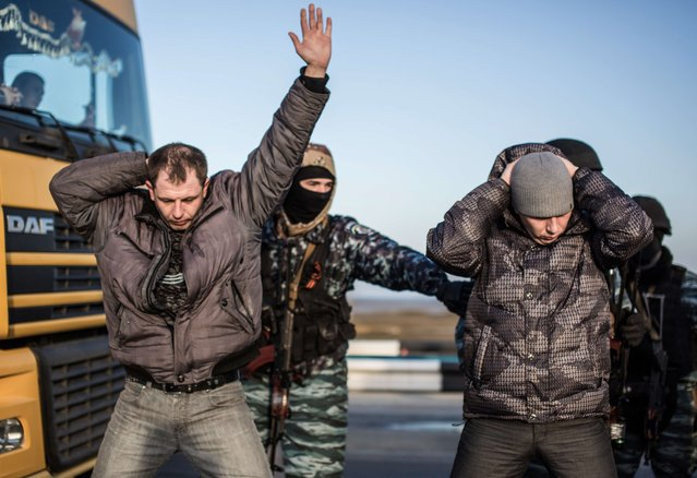 Men hold their hands up on their heads as they are searched by pro-Russian servicemen at Chongar checkpoint blocking the entrance to Crimea on March 10, 2014. Russia vowed on March 10 to unveil its own solution to the Ukrainian crisis that would run counter to US efforts and would appear to leave room for Crimea to switch over to Kremlin rule. (Photo by Alisa Borovikova/AFP Photo)