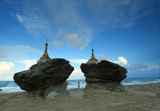 In this May 17, 2015, photo, two men walk past pagodas at Ngwe Saung beach, Pathein township, about 145 miles from Yangon, Myanmar. (Photo by Khin Maung Win/AP Photo)