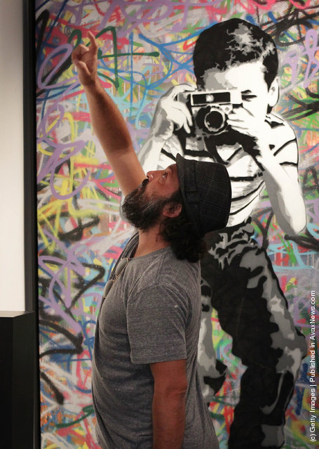 Artist Mr Brainwash stands in front of his painting  'Smile'  at the Opera Gallery