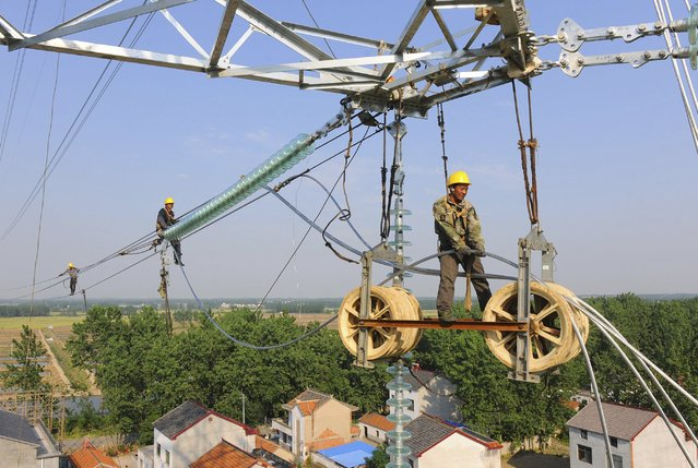 Workers install wires on an electricity pylon in Chuzhou, Anhui province, China, May 25, 2015. China's state planning agency on Monday released a list of more than 1,000 proposed projects totalling 1.97 trillion yuan ($317.75 billion) that it is inviting private investors to help fund, build and operate. (Photo by Reuters/China Daily)