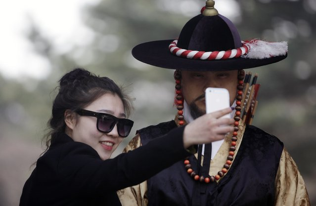 """A woman takes a """"selfie"""" with a man wearing the traditional Korean attire during the daily re-enactment for the changing of the Royal Guards at Deoksu Palace in central Seoul March 18, 2014. (Photo by Kim Hong-Ji/Reuters)"""