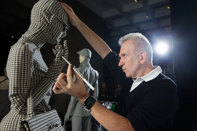 """Jean Paul Gaultier makes final preparations to items of couture on a revolving runway at the Barbican Centre on April 3, 2014 in London, England. """"The Fashion World of Jean Paul Gaultier: From the Sidewalk to the Catwalk"""" at the Barbican Art Gallery is the first major exhibition devoted to the celebrated French couturier, and runs from 9 April to 25 August. (Photo by Matthew Lloyd/Getty Images)"""