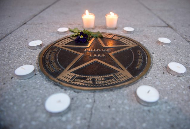 Candles lit in remembrance to Prince are seen around his star outside the Warner Theatre in Washington, DC on April 21, 2016. Emergency personnel tried and failed to revive music legend Prince, who died at age 57, after finding him slumped unresponsive in an elevator at his Paisley Park studios in Minnesota, the local sheriff said. (Photo by Andrew Caballero-Reynolds/AFP Photo)