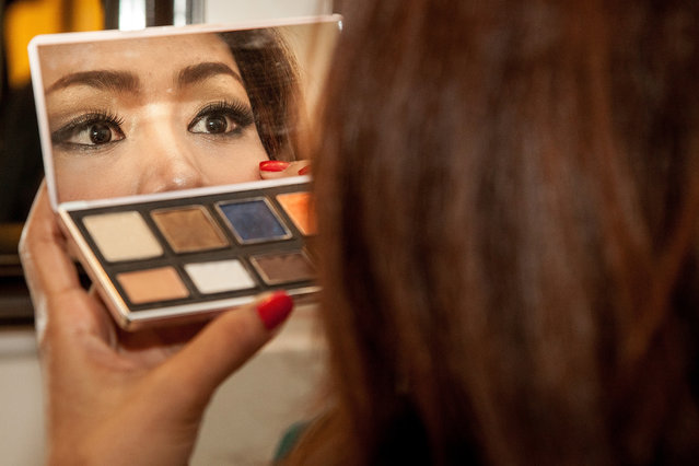 A professional model from Sun Model Agency finishes her make up backstage before modelling in a show at the Sofitel Hotel on March 30, 2014 in Phnom Penh, Cambodia. (Photo by Omar Havana/Getty Images)