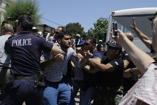 Police and coast guard scuffle with Syrians during a protest by refugees and migrants, demanding better living conditions and faster processing of their asylum registrations at the port of Mytilene, on the northern Greek island of Lesvos on Wednesday, June 17, 2015. The Aegean island has borne the brunt of a huge influx of migrants from the Middle East, Asia and Africa crossing from Turkey to nearby Greek islands. More than 50,000 migrants have arrived in Greece so far this year. (AP Photo/Thanassis Stavrakis)