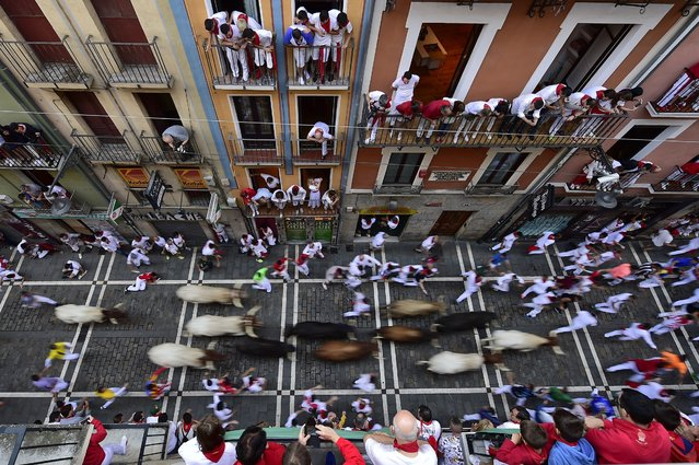 Revellers run next to fighting bulls during the running of the bulls at the San Fermin Festival, in Pamplona, northern Spain, Friday, July 12, 2019. Revellers from around the world flock to Pamplona every year to take part in the eight days of the running of the bulls. (Photo by Alvaro Barrientos/AP Photo)