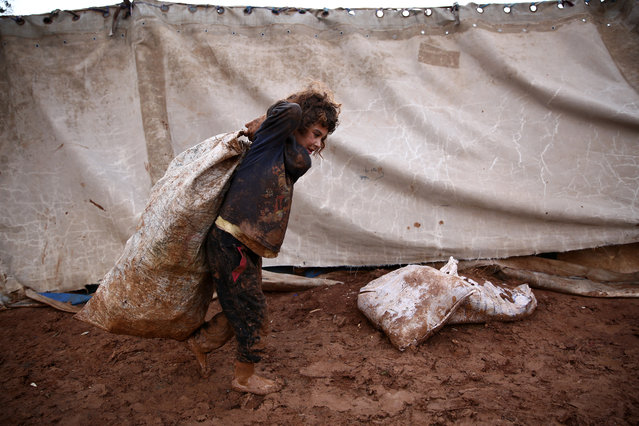 A Syrian child pulls over their back a sack while walking in the mud at a camp for the displaced near the village of Shamarin, near the border with Turkey in the northern Aleppo province, on December 6, 2018. (Photo by Nazeer Al-Khatib/AFP Photo)