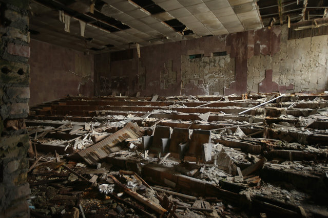 "Rotting wooden chairs stand under a collapsed ceiling in the damp and abandoned auditorium of the ""Energetika"" cultural center on September 29, 2015 in Pripyat, Ukraine. (Photo by Sean Gallup/Getty Images)"