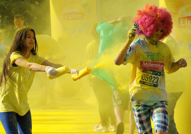 A runner gets a splash of colored powder during the Color Run, a 5km paint race that celebrates healthiness, happiness and individuality, in Warsaw, Poland, Saturday, June 27, 2015. (Photo by Alik Keplicz/AP Photo)