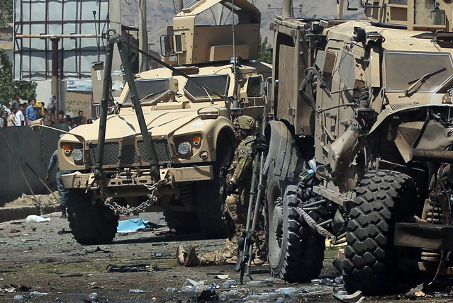 Armored vehicles remain at the site of a blast targeting the NATO convoy in Kabul, Afghanistan, Tuesday, June 30, 2015. (Photo by Massoud Hossaini/AP Photo)
