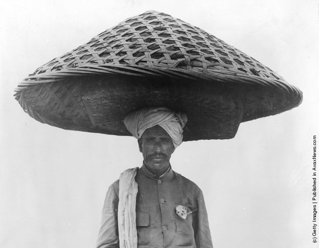 1934: A Singhalese man carrying a pile of clothing in a large closed basket on his head that looks like an enormous mushroom shaped hat