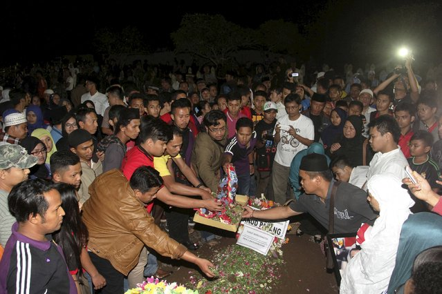 Family and relatives attend the funeral of Indonesian Airforce officer Riri Setiawan, who was killed in this week's crash of a C-130 Hercules aircraft in Medan, at the Heroes Cemetery, Tanah Datar, West Sumatra, Indonesia July 1, 2015 in this photo taken by Antara Foto. Picture taken July 1, 2015. (Photo by Muhammad Arif Pribadi/Reuters/Antara Foto)