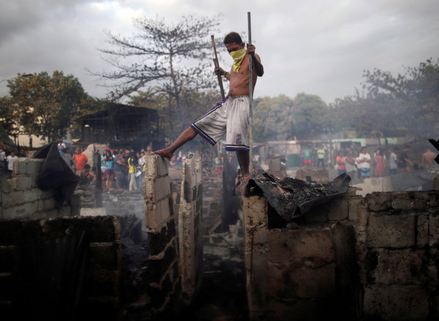 A Filipino informal settler manuevers on top of burnt shanties after a fire at a slum area in Paranaque city, south of Manila, Philippines, 22 February 2019 (issued 13 June 2019). The metropolitan area of Manila has the largest slum area in the world, home to some four million people, a third of the inhabitants of the city, according to studies conducted by humanitarian organization. (Photo by Francis R. Malasig/EPA/EFE)