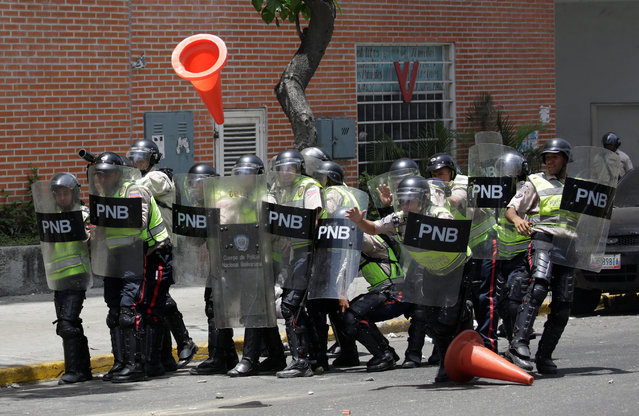 Police officers protect themselves from traffic cones thrown by demonstrators during clashes with security forces during an opposition rally in Caracas, Venezuela on April 4, 2017. (Photo by Marco Bello/Reuters)