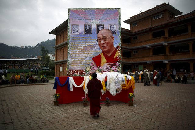 A Tibetan monk offers prayers in front of the portrait of Dalai Lama during his 80th birthday celebration in Kathmandu July 6, 2015. (Photo by Navesh Chitrakar/Reuters)