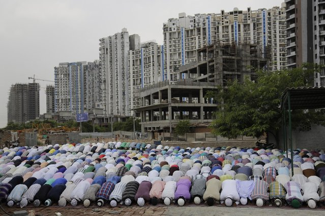 Indian Muslims offer prayers during Ramadan as new under construction houses are seen in the background in the outskirts of New Delhi, India, Friday, July 3, 2015. (Photo by Altaf Qadri/AP Photo)