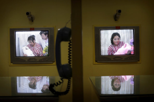 Mothers with their newborn babies are seen on a television screen of a video conference station, used to separate and protect mothers and newborns from visitors' germs, at Pyongyang Maternity Hospital during a press tour on Saturday, May 7, 2016 in Pyongyang, North Korea. (Photo by Wong Maye-E/AP Photo)
