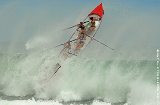 The Piha Womens crew battle a large wave during the Day of Giants Surfboat race regatta at Piha beach