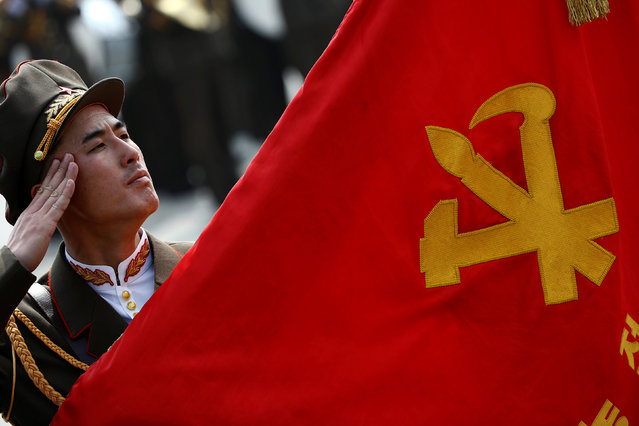 A soldier salutes a Workers' party flag during a military parade marking the 105th birth anniversary of country's founding father Kim Il Sung in Pyongyang, North Korea, April 15, 2017. (Photo by Damir Sagolj/Reuters)