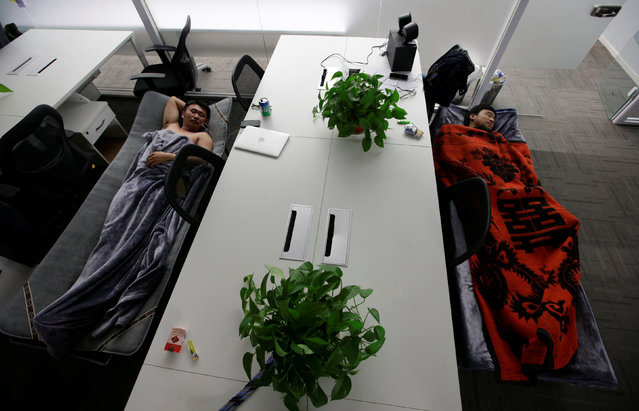 Han Liqun (L), HR manager of RenRen Credit Management Co., and IT engineer Xiang Siyang sleep on camp beds at the office after finishing work early morning, in Beijing, China, April 27, 2016. (Photo by Jason Lee/Reuters)