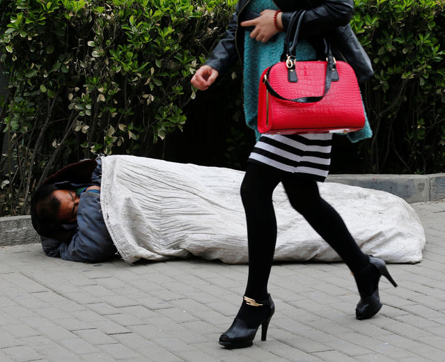 A woman walks past a homeless man sleeping on the street in Beijing April 22, 2013. (Photo by Kim Kyung-Hoon/Reuters)