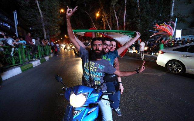 Iranian wave the national flag during celebration in northern Tehran on July 14, 2015, after Iran's nuclear negotiating team struck a deal with world powers in Vienna. Iranians poured onto the streets of Tehran after the Ramadan fast ended at sundown Tuesday to celebrate the historic nuclear deal agreed earlier with world powers in Vienna. (Photo by Atta Kenare/AFP Photo)