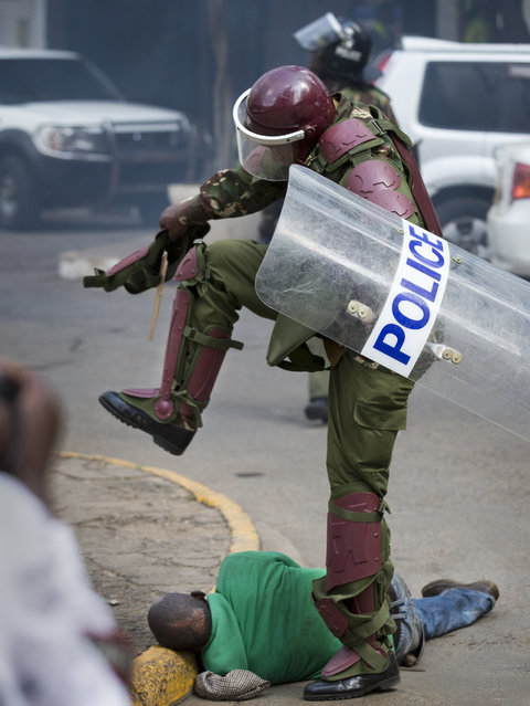 A Kenyan riot policeman repeatedly kicks a protester as he lies in the street after tripping over while trying to flee from them, during a protest in downtown Nairobi, Kenya Monday, May 16, 2016. (Photo by Ben Curtis/AP Photo)