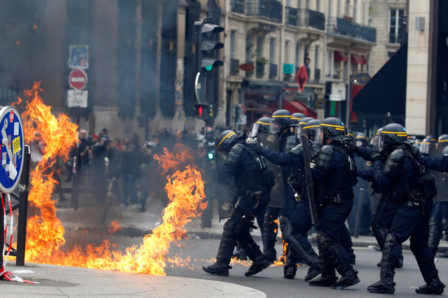 French CRS riot police protect themselves from flames during clashes at the traditional May Day labour union march in Paris on May 1, 2017. (Photo by Gonzalo Fuentes/Reuters)