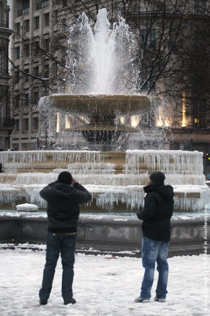 Visitors take phone pictures of the frozen fountains in Trafalgar Square