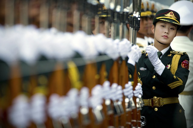 An officer reviews members of the honor guard as they line up before a welcoming ceremony for visiting Mozambique's President Filipe Jacinto Nyusi at the Great Hall of the People in Beijing, Wednesday, May 18, 2016. (Photo by Mark Schiefelbein/AP Photo)