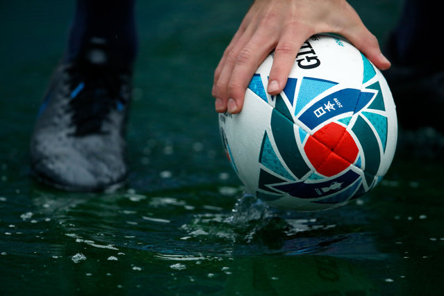A rugby ball is seen in a puddle of rainwater during the South Africa Captain's Run session at the International Stadium Yokohama in Yokohama on October 25, 2019, ahead of the Japan 2019 Rugby World Cup semi-final match against Wales. (Photo by Odd Andersen/AFP Photo)