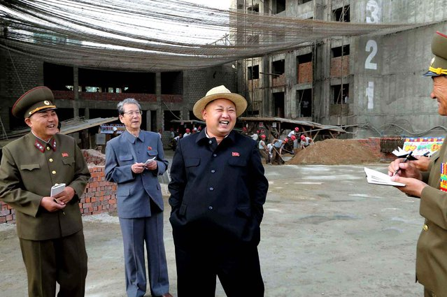 This undated picture released from North Korea's official Korean Central News Agency (KCNA) on May 21, 2013 shows North Korean leader Kim Jong-Un (2nd R) visiting the construction site of apartment houses for educators of the Kim Chaek University of Technology in Pyongyang. (Photo by AFP Photo/KCNA via KNS)