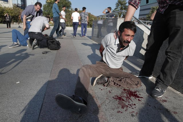 A protester that tried with others to stage a march  to denounce the deaths of a Monday explosion in the Turkish town of Suruc near the Syrian border, yells as he bleeds after being wounded while Turkish police were arresting him in Istanbul, Tuesday, July 21, 2015. (Photo by Lefteris Pitarakis/AP Photo)