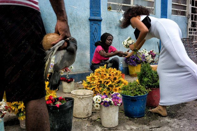 A woman dressed in white buys flowers while her companion holds a live pigeon and a coconut in preparation for a Santeria animal sacrifice ceremony May 2, 2016, in Old Havana, Cuba. Popular in Cuba, Santeria is an African-Caribbean religion with some Roman Catholic elements. (Photo by Dotan Saguy)