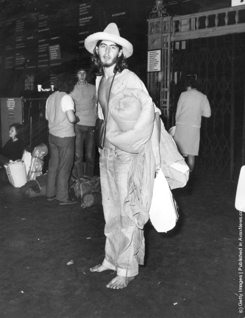 1970: A shoeless hippy at Waterloo Railway Station, London, waiting for a train to the Isle of Wight before the start of the Isle of Wight festival