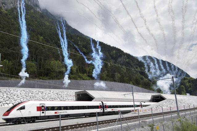 The first train comes out of the tunnel's North portal on the opening day of the Gotthard rail tunnel,  at the North portal near Erstfeld, Switzerland, Wednesday, June 1, 2016. (Photo by Laurent Gillieron/Keystone via AP Photo)