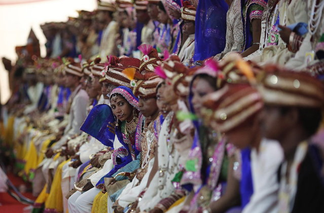 Brides and grooms pose for pictures during a mass wedding ceremony at Ramlila ground in New Delhi June 15, 2014. A total of 92 physically challenged couples of all religions from across India took their wedding vows on Sunday during the mass wedding ceremony organised by a non-governmental organisation (NGO), organisers said. (Photo by Adnan Abidi/Reuters)