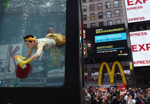 "Performance artist Annie Saunders performs ""Cleaning"" during a press preview from Holoscenes, a performance- installation in Times Square on May 31, 2017 in New York. The event is created by the artist Lars Jan and his company Early Morning Opera, that features a cast of performers in a twelve- ton, 8' x 6' x 10' glass aquarium and viscerally connects everyday actions to climate change. Times Square Arts and the World Science Festival are launching the event called Science in the Square, a four- day event that brings science – and climate science in particular. (Photo by Timothy A. Clary/AFP Photo)"