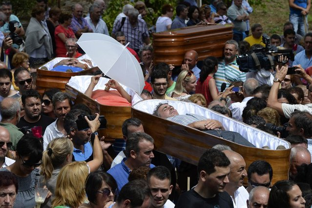 "People are carried in coffins by relatives during the annual ""Procession of the Shrouds"" to celebrate Santa Martha ""the saint of resurrection"" in the village of Santa Marta de Ribarteme, northwestern Spain, on July 29, 2015. People who have escaped death lie in caskets and are carried in procession by relatives in a gesture of thanks for being kept alive. (Photo by Miguel Riopa/AFP Photo)"