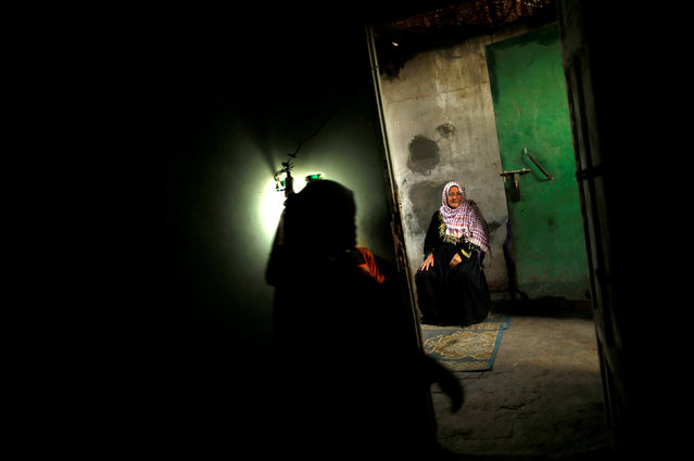 A Palestinian woman sits inside her house lit by a lamp powered by a battery during a power cut in Beit Lahiya town in the northern Gaza Strip May 2, 2016. (Photo by Mohammed Salem/Reuters)