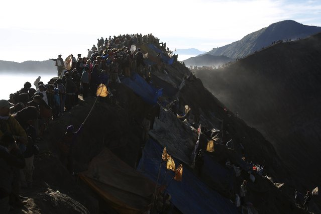 People stand on top of the crater of Mount Bromo to attend the Kasada Festival in Probolinggo, Indonesia's East Java province, August 1, 2015. (Photo by Reuters/Beawiharta)