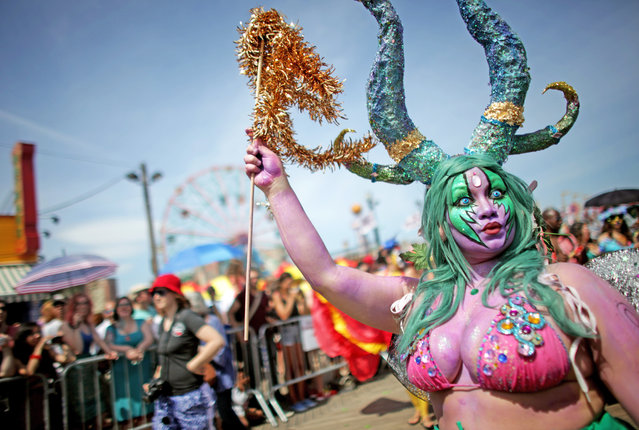 Participant Amanda Berrios walks the boardwalk in the 2014 Mermaid Parade at Coney Island on June 21, 2014 in the Brooklyn borough of New York City. The Mermaid Parade began in 1983 and features participants dressed as mermaids and other sea creatures while paying homage to the former tradition of the Coney Island Mardi Gras which ran annually in the early fall from 1903-1954. (Photo by Yana Paskova/Getty Images)