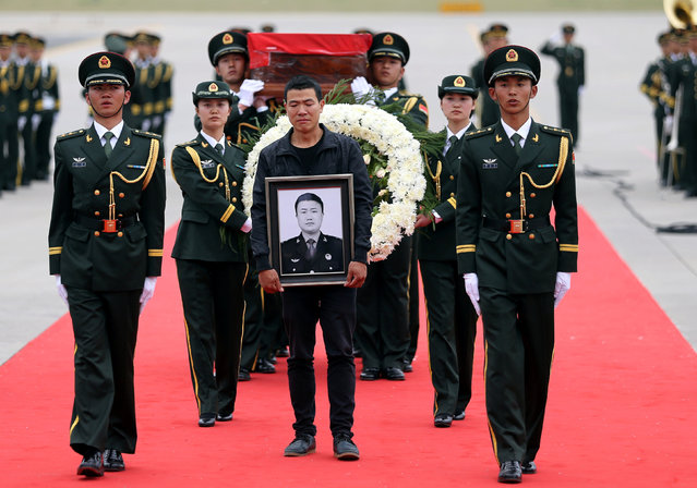 A relative holds a picture of Shen Liangliang, a Chinese peacekeeper killed in Mali, during a body returning ceremony held at an airport in Changchun, Jilin province, June 9, 2016. (Photo by Reuters/China Daily)