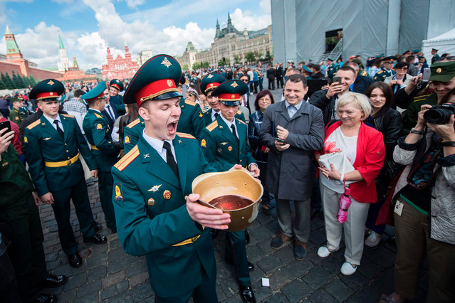 Graduates of the Moscow Military Commanders Training School drink sparkling wine from a helmet during their graduation ceremony at Red Square in Moscow on June 23, 2017. (Photo by Natalia Kolesnikova/AFP Photo)