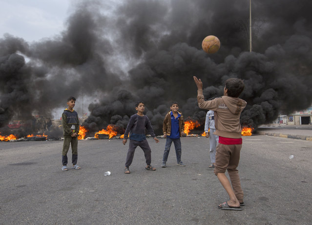 Iraqi children play with a ball on a street blocked with burning tyres, amid a general strike in the southern city of Basra, on November 25, 2019. The demonstrations rocking the capital and Shiite-majority south since October 1 are the biggest grassroots movement the country has seen in decades. Sparked by outrage over rampant government corruption, poor services and lack of jobs, they have since gone straight to the source: calling out the ruling system as inherently flawed and in need of a total overhaul. (Photo by Hussein Faleh/AFP Photo)