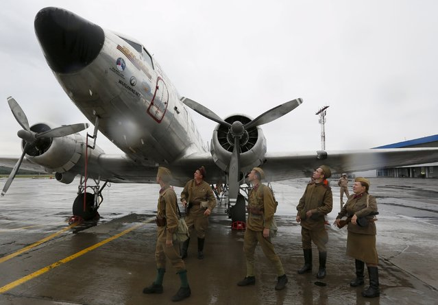 Enthusiasts dressed in vintage Soviet uniforms gather near a U.S. Douglas C-47 Dakota military transport airplane constructed in the early 1940s, after it landed during a transcontinental flight on the Alaska-Siberia route, at Yemelyanovo International Airport outside the Siberian city of Krasnoyarsk, Russia, August 4, 2015. (Photo by Ilya Naymushin/Reuters)