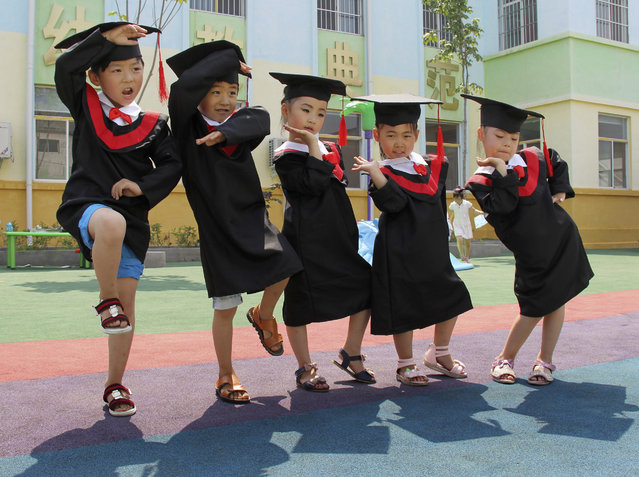 Children in gowns and mortarboards pose for pictures during their kindergarten graduation ceremony, in Wenxian county, Henan province July 2, 2014. (Photo by Reuters/Stringer)